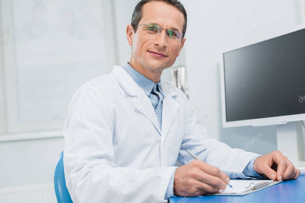 Doctor filling checklist by computer in modern clinic