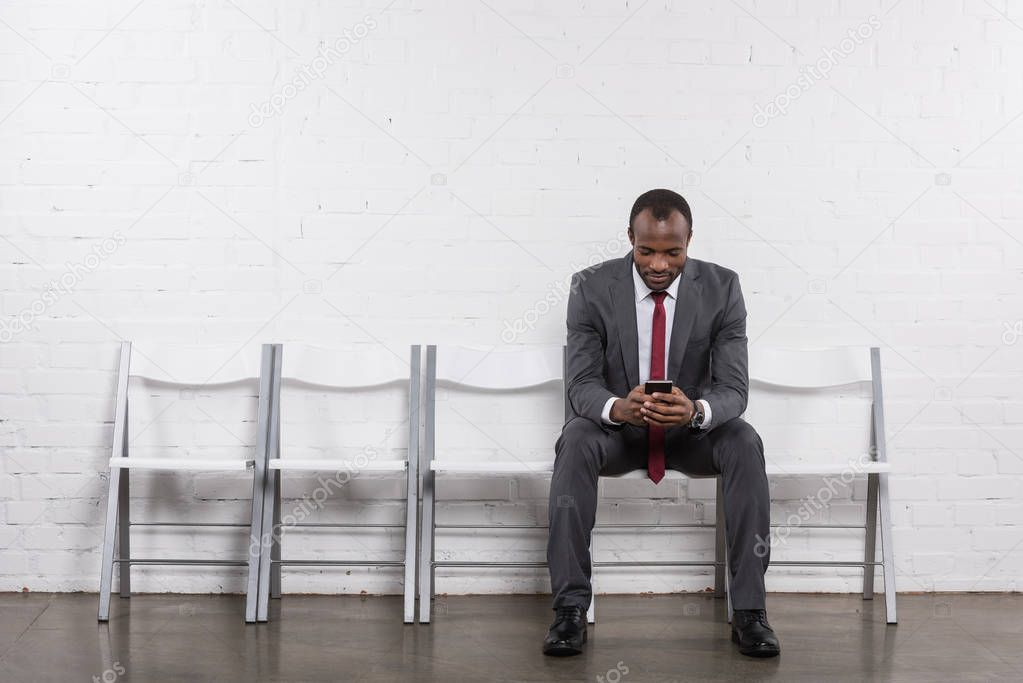African american businessman with smartphone waiting for job interview