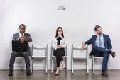 multiethnische junge Geschäftsleute sitzen auf Stühlen, während sie auf ein Vorstellungsgespräch warten