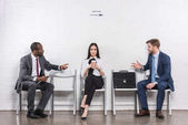 donna di affari asiatica ascoltando multiculturali uomini daffari che hanno conversazione durante lattesa per il colloquio di lavoro