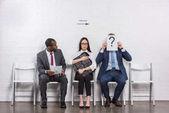 Fotografie Kaufmann für Gesicht mit Karte mit Fragezeichen während des Wartens auf Job-Interview mit multiethnischen Geschäftsleute