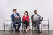 Fotografie multiethnic business people sitting on chairs while waiting for job interview