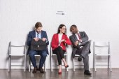 multiethnic business people sitting on chairs while waiting for job interview