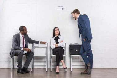 multiethnic business people having conversation while waiting for job interview