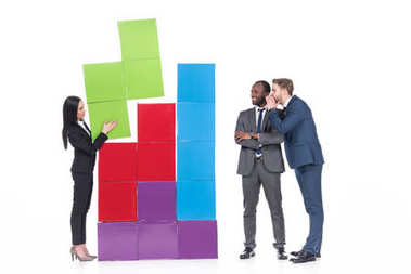 multicultural businessmen looking at asian businesswoman collecting colorful blocks isolated on white