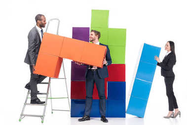 multiethnic business colleagues collecting colorful blocks isolated on white, business cooperation concept