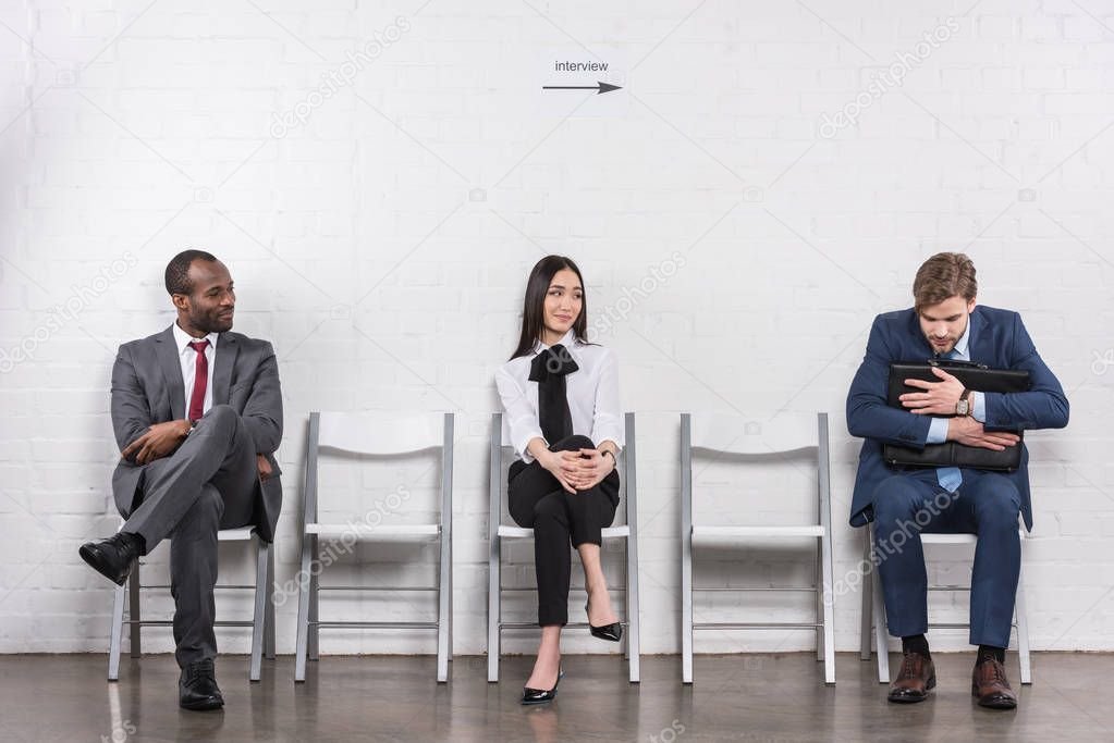 multiethnic young business people sitting on chairs while waiting for job interview