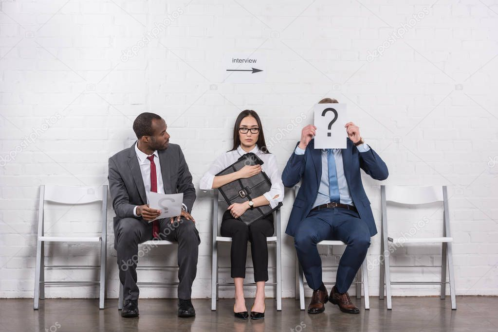 businessman covering face with card with question mark while waiting for job interview with multiethnic business people