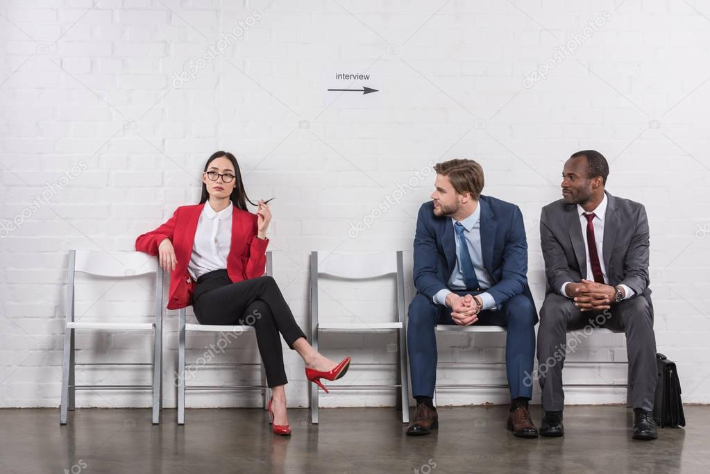 multicultural businessmen looking at asian businesswoman while waiting for job interview