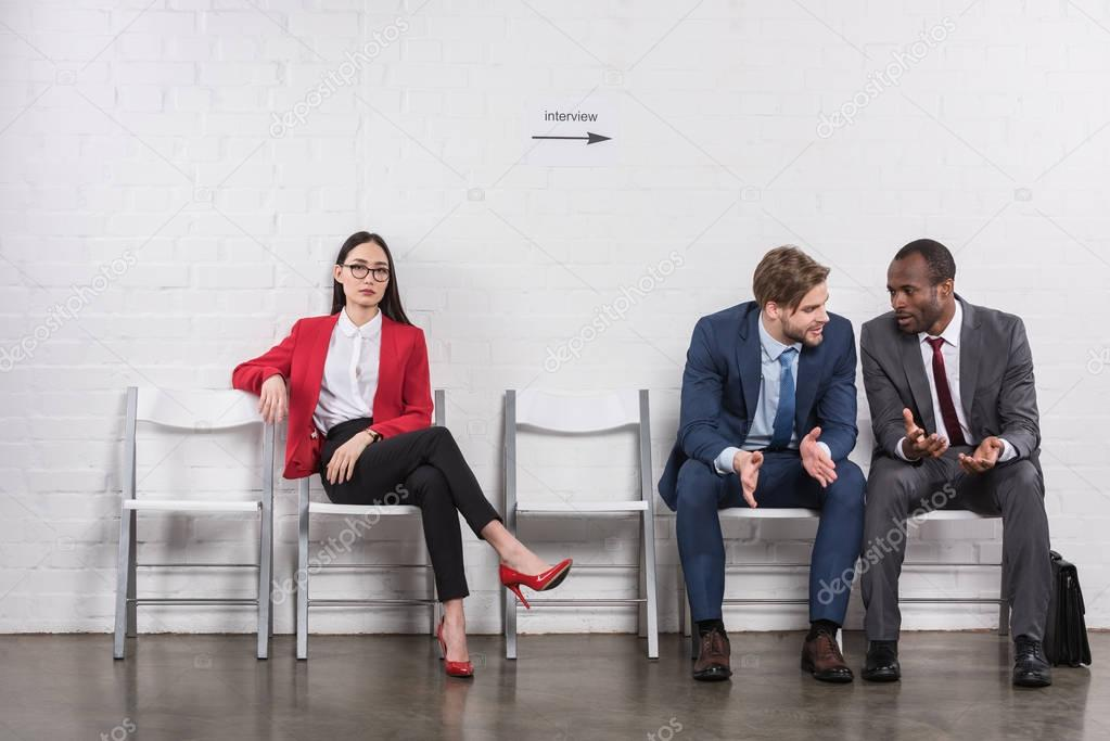 multicultural businessmen having conversation near asian businesswoman while waiting for job interview