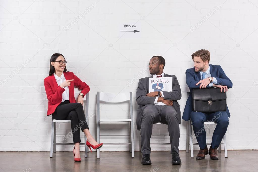 smiling asian businesswoman pointing at multiethnic businessmen while waiting for job interview