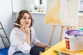 Fényképek Fiatal kreatív lány álmodik a festőállvány a könnyű stúdió