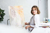 Young creative girl dreaming by easel in light studio