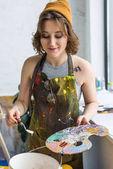 Mladá dívka kreativní práci s spachtle a palety v světelné studio