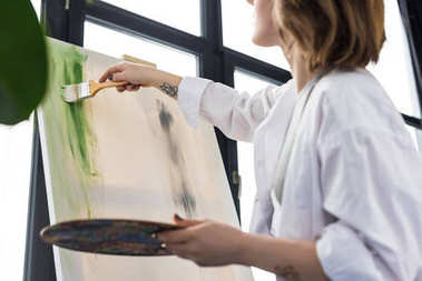 Young artistic girl working by easel in light studio