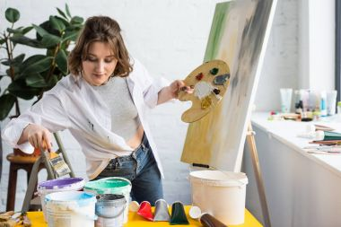 Young artistic girl choosing paint in light studio