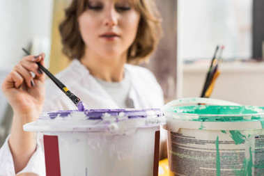 Young creative girl dunks a paintbrush into the paint in light studio