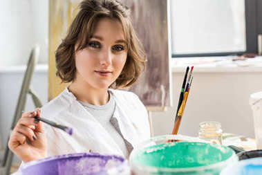 Young artistic girl dunks a paintbrush into the paint in light studio