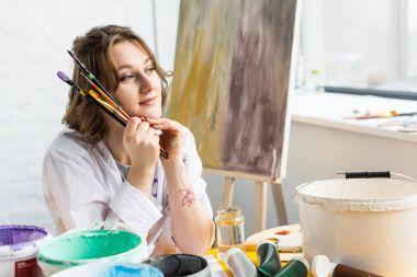 Young artistic girl looking away in light studio