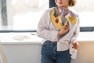 Young inspired girl holding palette in light studio