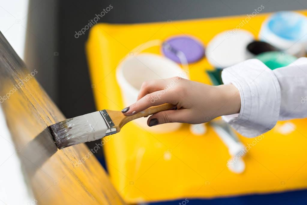 Young artistic girl painting on canvas in light studio
