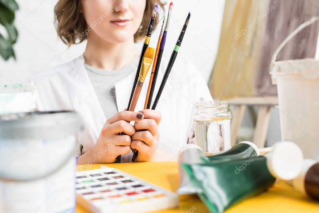 Close-up view of young artistic girl with brushes in hands in light studio