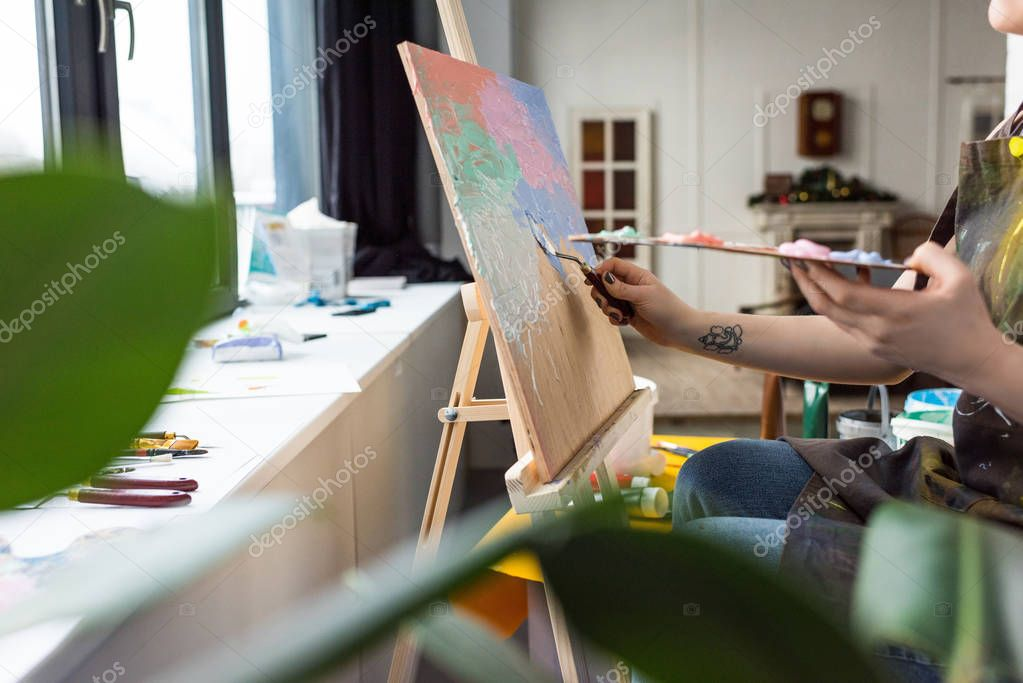 Close-up view of young creative girl applying primer on canvas in light studio