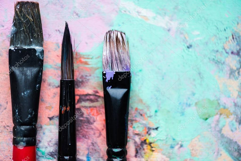 Close-up view of artistic brushes on palette covered with colorful paint spots