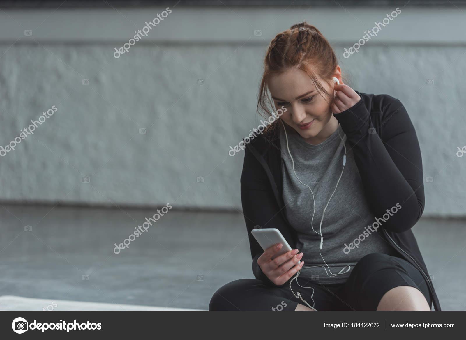 fille ob se couter musique sur smartphone dans salle gym photographie allaserebrina 184422672. Black Bedroom Furniture Sets. Home Design Ideas
