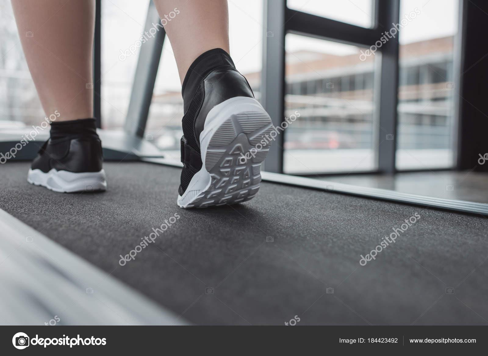 Крупным планом зрения полных девочка ноги беговой дорожке.