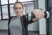 Fotografie übergewichtige Mädchen heben Hantel im Fitnessstudio
