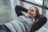Obézní dívka provedení sit ups v tělocvičně