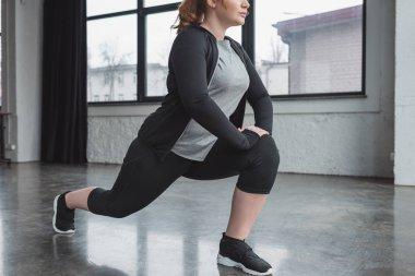 Curvy girl in gym stretching legs