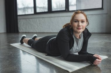 Obese girl lying on floor and looking at camera in gym