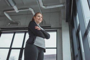 Obese girl in sportswear standing by window in gym