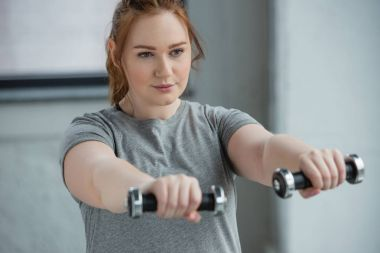Overweight girl exercising with dumbbells in gym