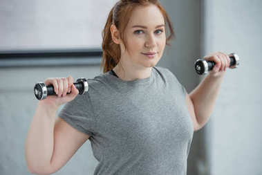Overweight girl lifting dumbbells in gym