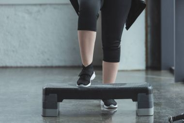 Curvy girl exercising on step platform in gym