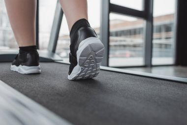 Close-up view overweight girl feet on treadmill in gym
