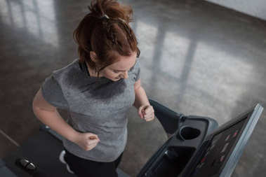 Overweight girl running on treadmill in gym