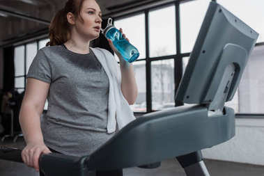 Curvy girl drinking from water bottle while running on treadmill in gym