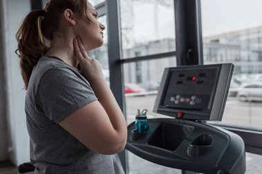 Overweight girl checking pulse during run on treadmill in gym