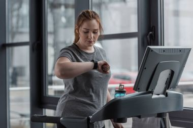 Overweight girl looking at fitness tracker while running on treadmill in gym