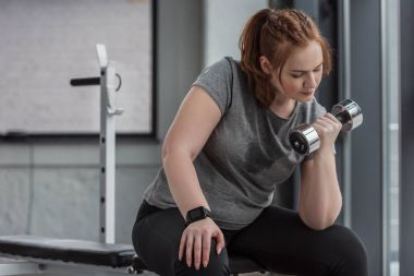 Curvy girl training with dumbbell in gym