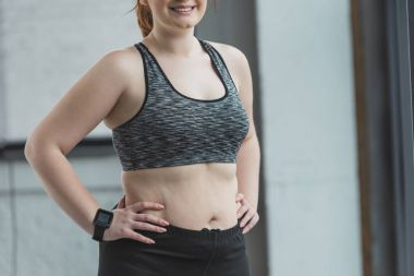 Close-up view of smiling overweight girl in gym