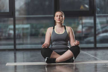 Curvy girl during meditation in gym
