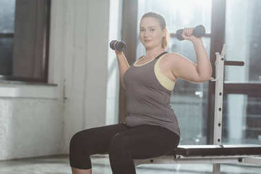 Curvy girl training with dumbbells in gym
