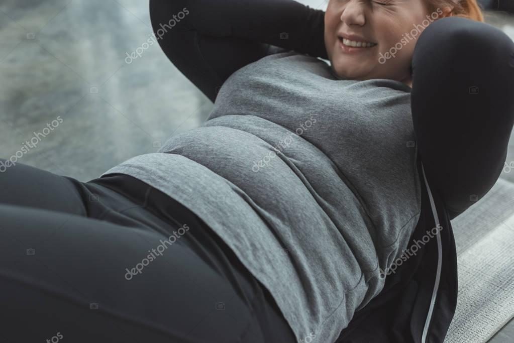 Close-up view of curvy girl performing sit ups in gym