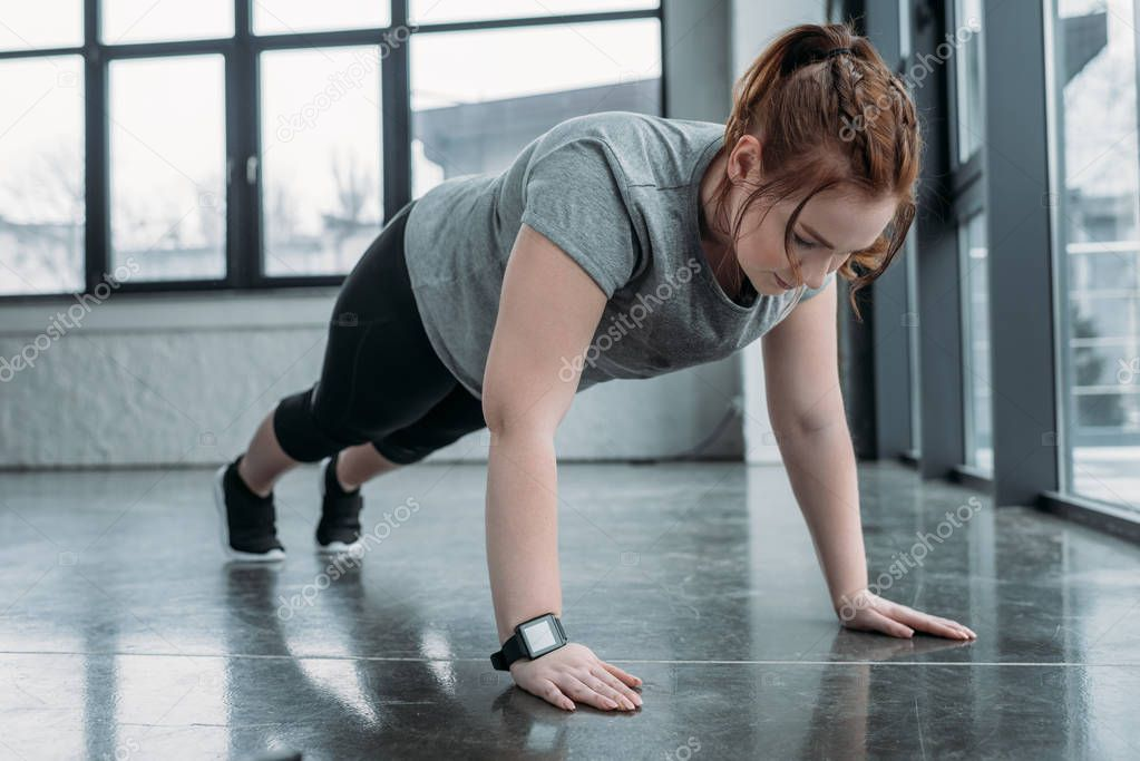 Overweight girl performing push ups in gym