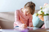 Fotografie Child with down syndrome drawing with pencil while sitting on sofa